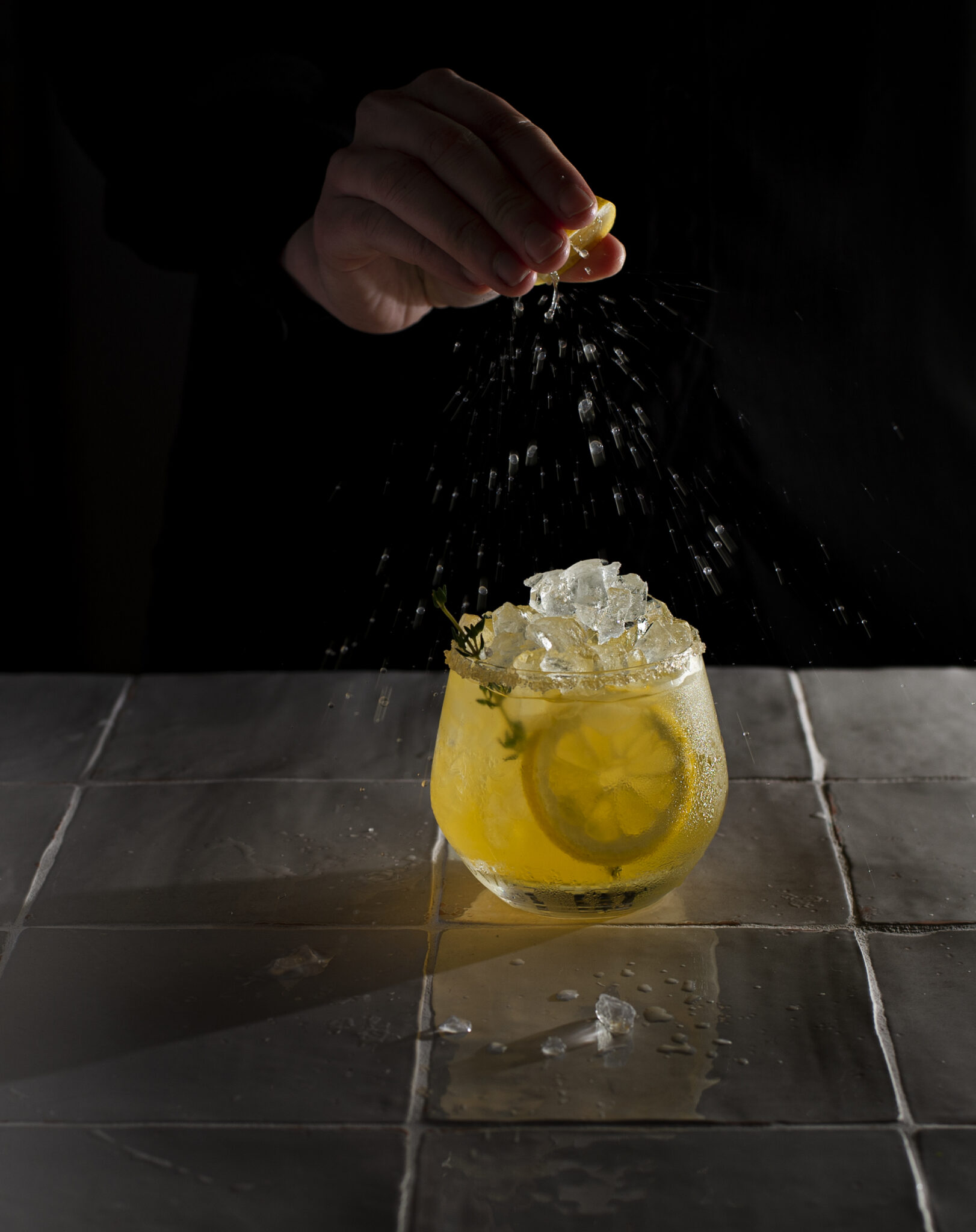 squeezing lemon juice in cocktail