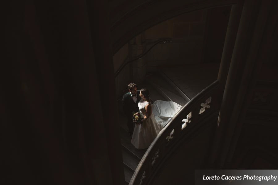 Bride and groom in staircase with a shadow.
