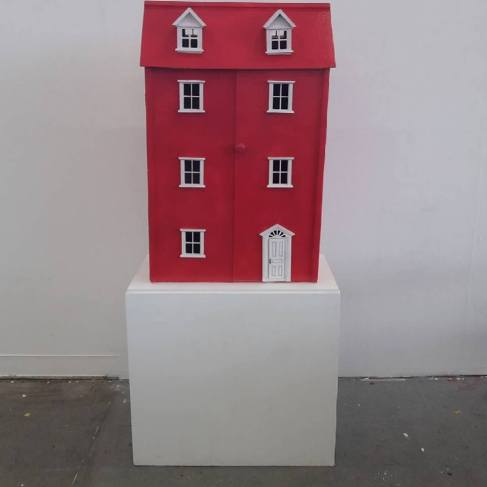 My red dollhouse displayed on the white newly painted plinth