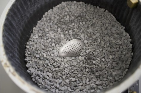 Cranial plate being processed in a mass finishing bowl.