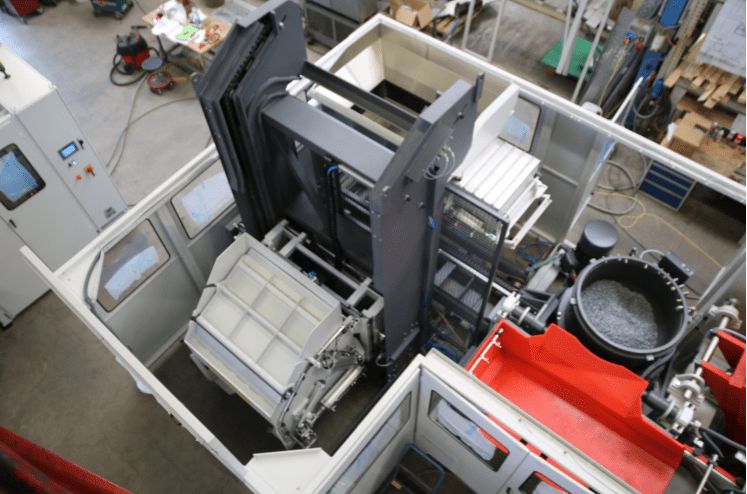 A lift and tip loader with integrated vibratory hopper is included in this Rosler FKS mass finishing system.