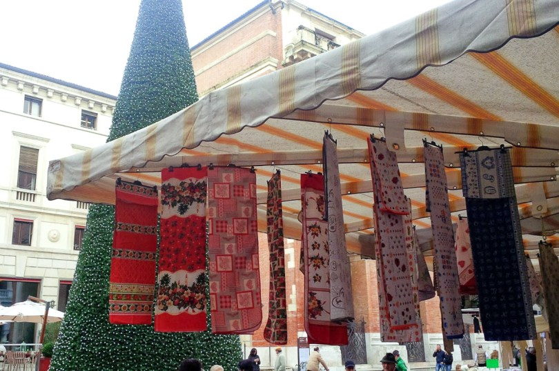 Market stall selling tableclothes with Christmas patterns- Vicenza, Italy - rossiwrites.com