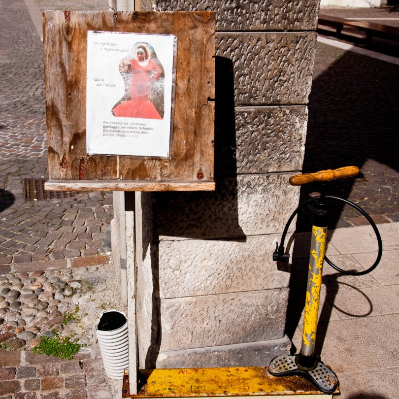Warning sign and a pump by a bicycle shop, Vicenza, Veneto, Italy