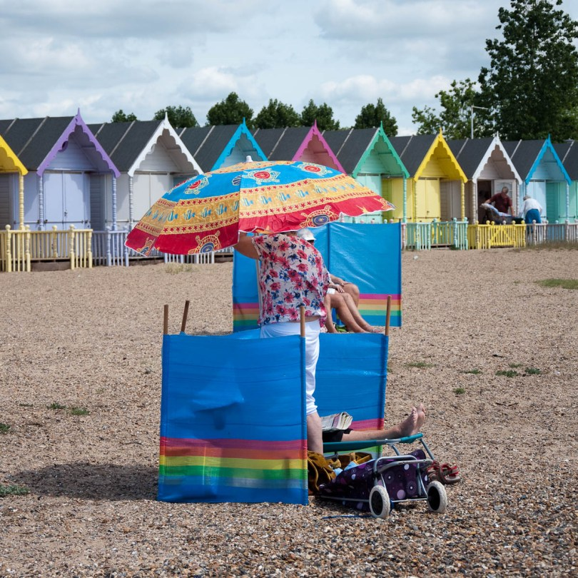 Opening a beach umbrella at the beach, Mersea Island, Essex, England - www.rossiwrites.com