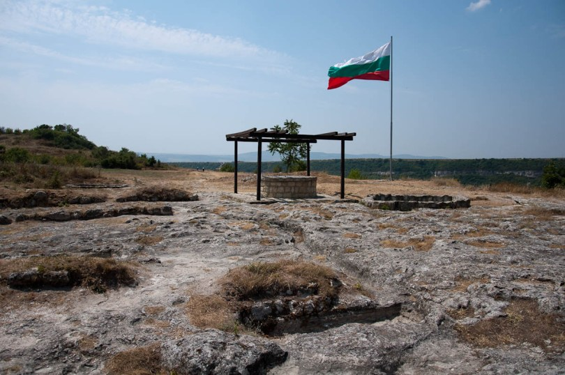 The Bulgarian flag, a well and the remnants of the medieval Metropolitan church, Ovech Fortress, Provadia, Bulgaria - www.rossiwrites.com