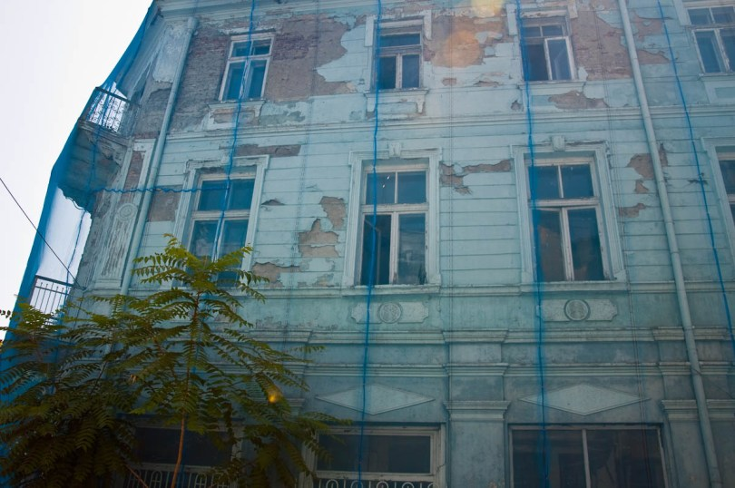 dilapidated-light-blue-house-covered-with-a-protective-net-varna-bulgaria-www.rossiwrites.com