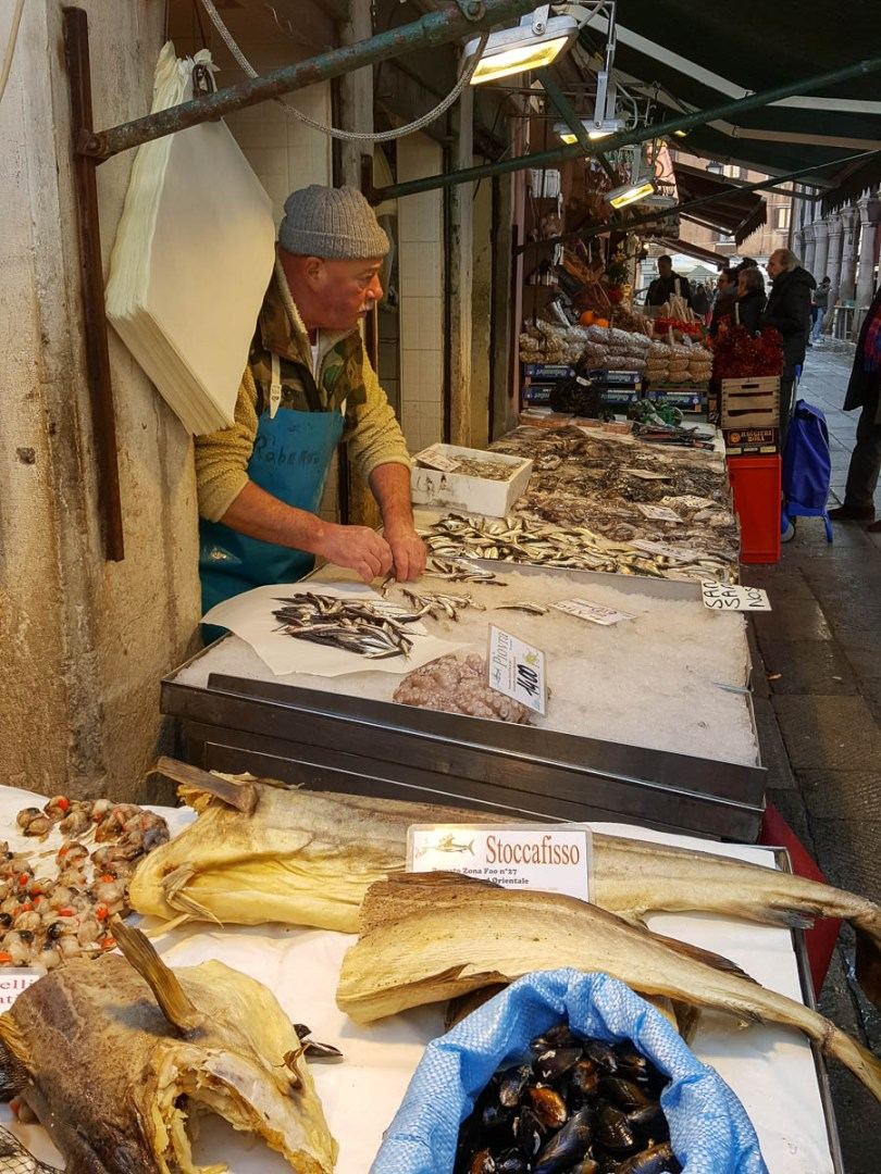 A fishmonger at work - Rialto Fish Market, Venice, Italy - www.rossiwrites.com