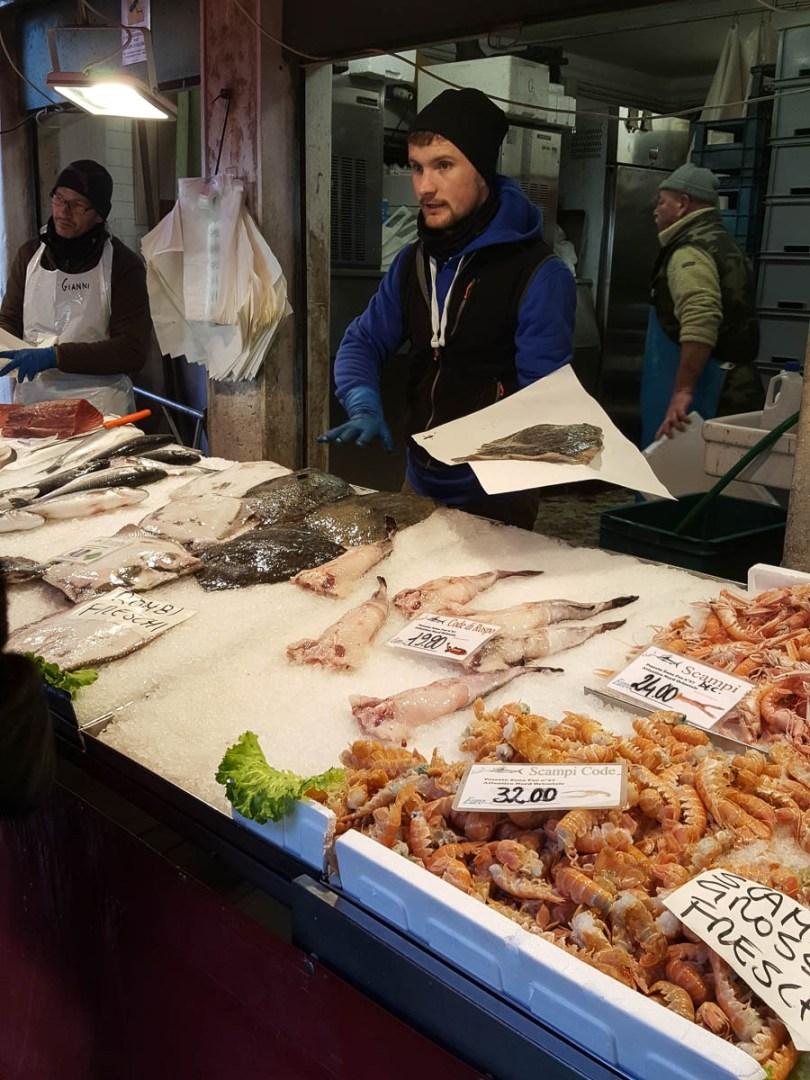 A fishmonger selling fish - Rialto Fish Market, Venice, Italy - rossiwrites.com