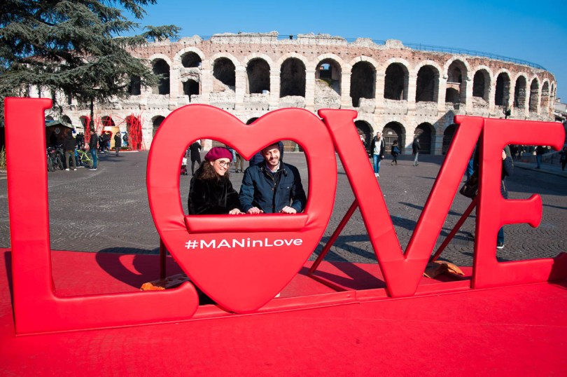 Arena di Verona with a big LOVE sign and a couple in love - Verona, Italy - www.rossiwrites.com