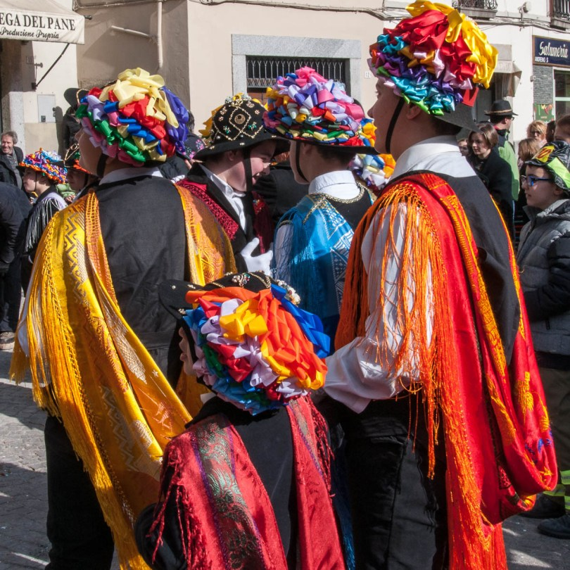 Men and kids in traditional dress with long colourful scarves - Bagolino, Lombardy, Italy - www.rossiwrites.com