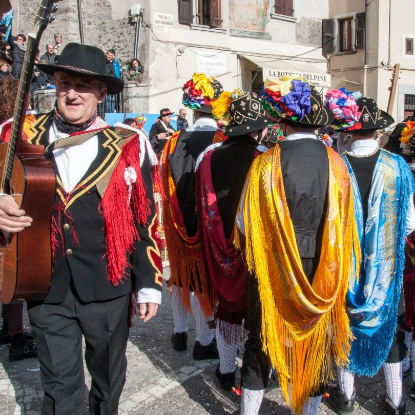 Men in traditional dress with long colourful scarves - Bagolino, Lombardy, Italy - www.rossiwrites.com