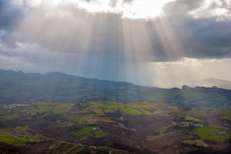 The sun coming through the clouds above the green hills that surround San Marino - rossiwrites.com