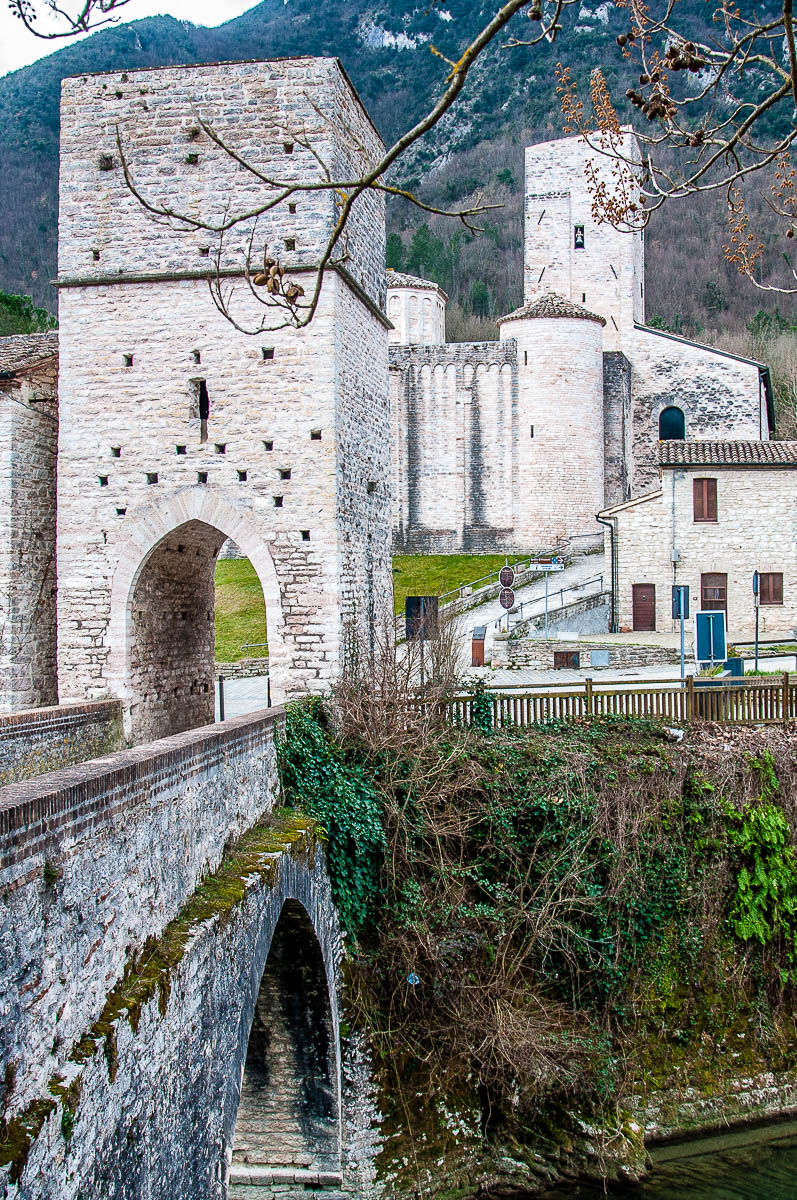 The Roman bridge over the river Sentino with the Abbey of San Vittore delle Chiuse - Marche, Italy - rossiwrites.com