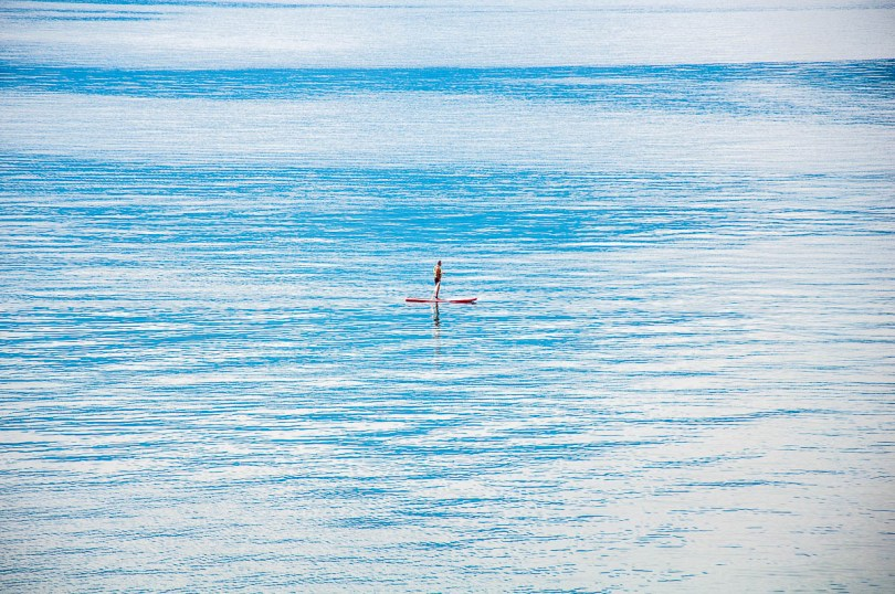 A person on a paddleboard on Lake Garda - Torri del Benaco, Italy - rossiwrites.com