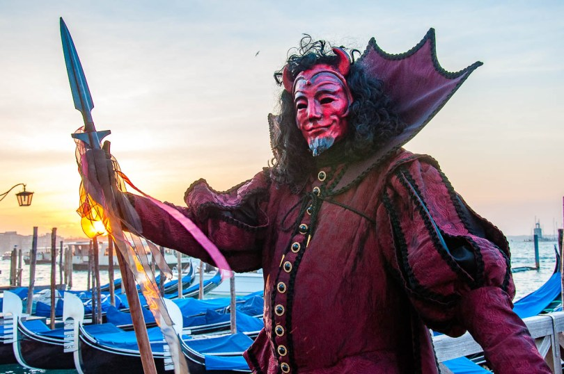 A Devil mask standing in front of the St. Mark's Basin - Venice, Italy - rossiwrites.com