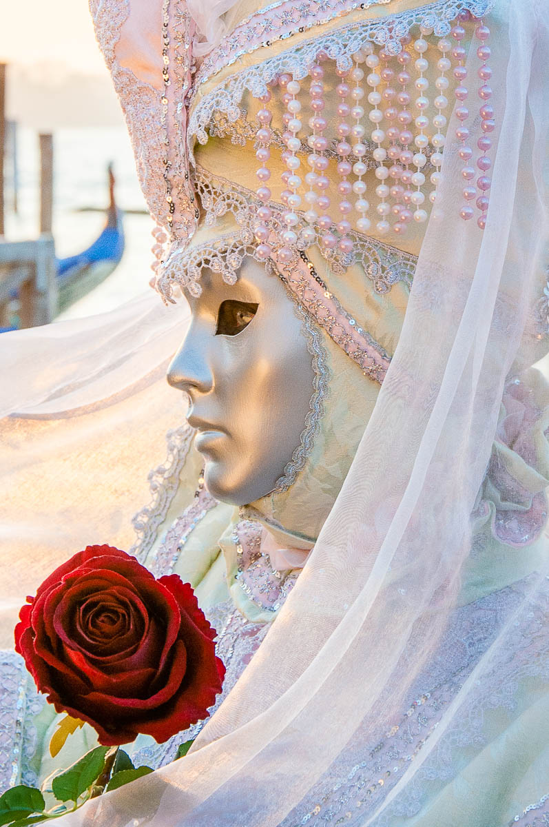 A beautiful mask holding a rose in front of the St. Mark's Basin - Venice, Italy - rossiwrites.com