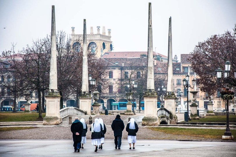 A group of nuns and priests walking towards the bridge with the obelisks on Prato della Valle - Padua, Italy - rossiwrites.com