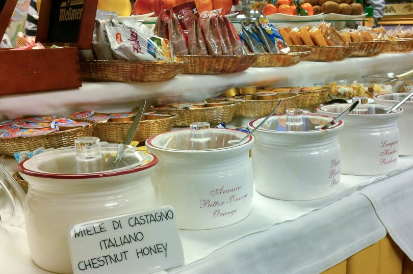 A table with different honeys, jams, and rusks at a hotel in Italy - rossiwrites.com
