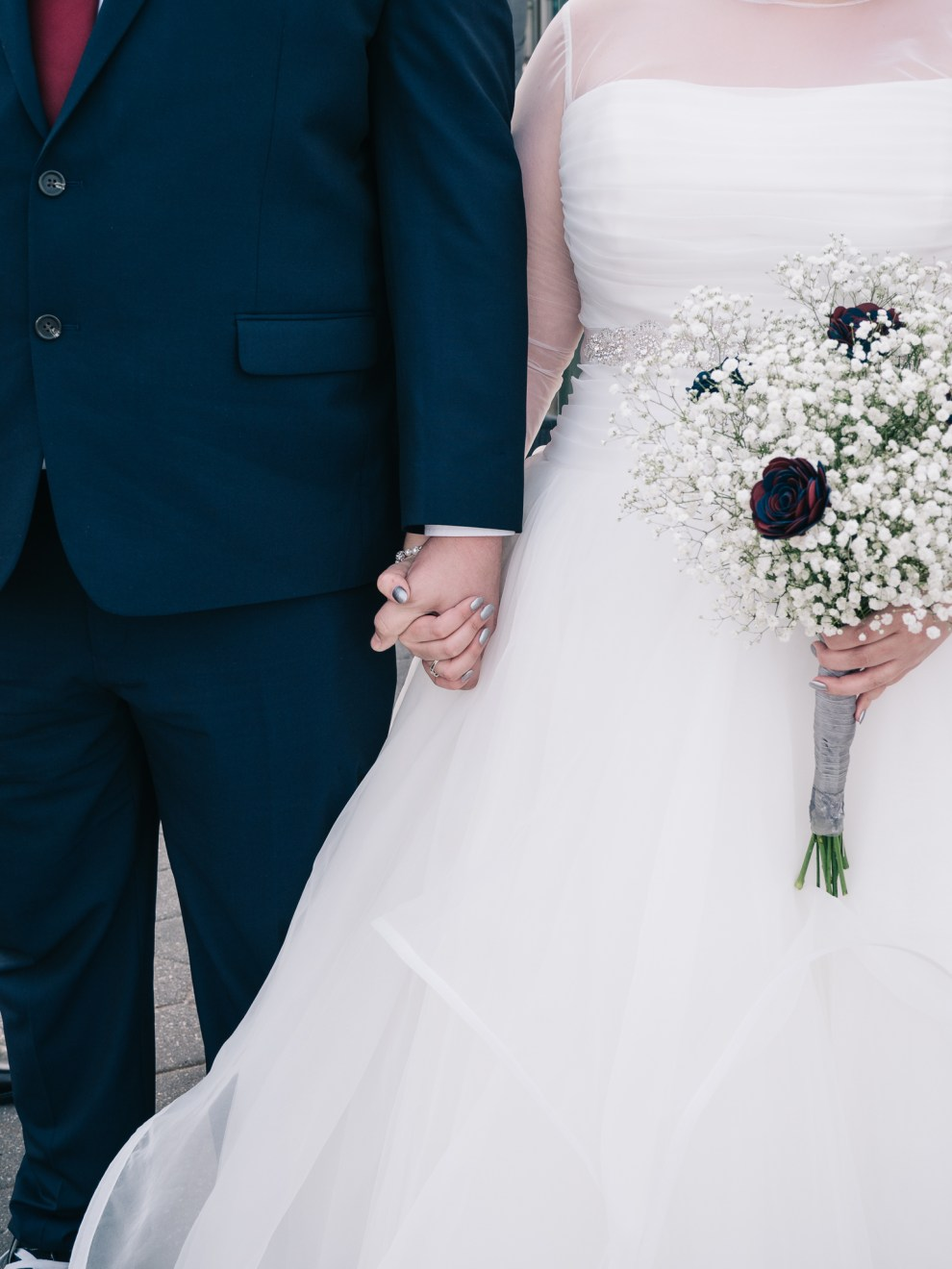 bride and groom holding hands with baby breath bouquet