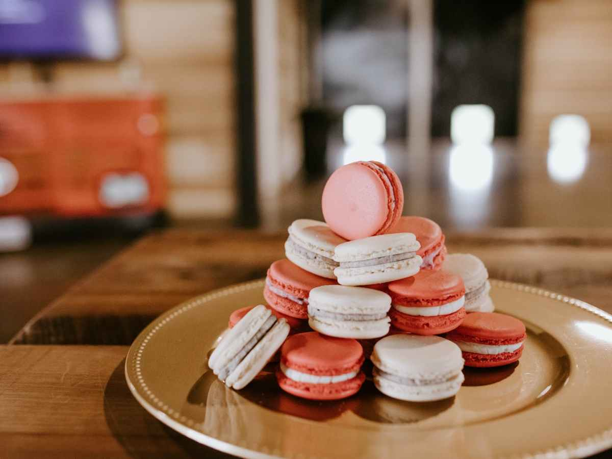 sweet macaroons on round plate on wooden table