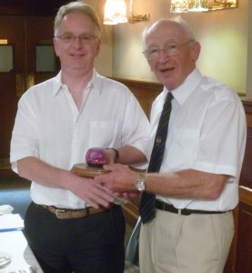Secretary Craig Wilson receives Rotarian of the Year award from outgoing President Neil Beattie.