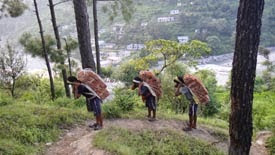 Labourers carry bricks on the steep incline to this school.