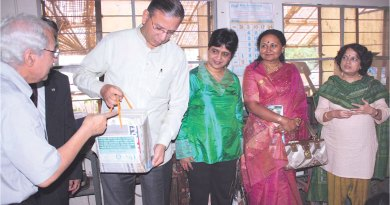 PRIP K R Ravindran looks at a paper bag while Rtn Surendra Shroff briefs  him about it. Vanathy Ravindran (extreme right) is also in the picture.