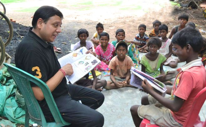 A Rotarian teaches children in a West Bengal village.