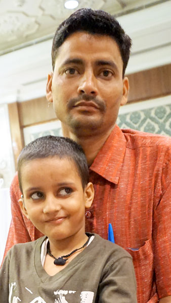 Little Sandesh is all ears, sitting on his father's lap, post the cochlear implant.