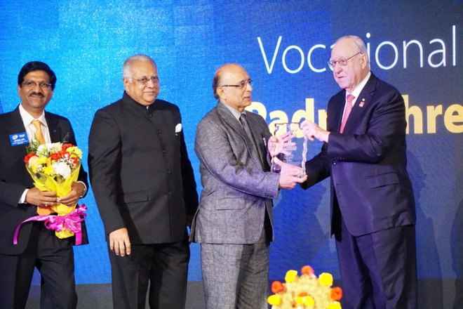 RI President John Germ honours Dr J M Hans with the Vocational Service Award in the presence of RID Manoj Desai and DG Sharat Jain.