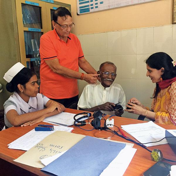 Team leader Gopal Sapra fixes hearing aid in a patient's ear.