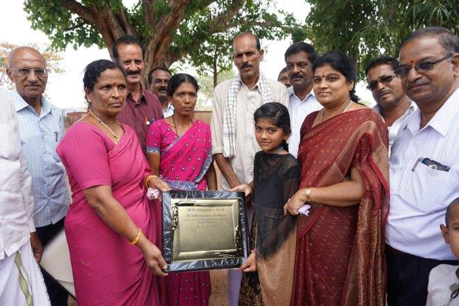 Suchitra displays the DCW Award in the presence of her parents Prabhu and Geetha (centre), Z P member Rathnamma, Rtn C V Srinivas Shetty, Club President G Guruswamy, Rtn Prabhakar, Gram Panchayat President Nagalambika and headmaster Shivakumar.