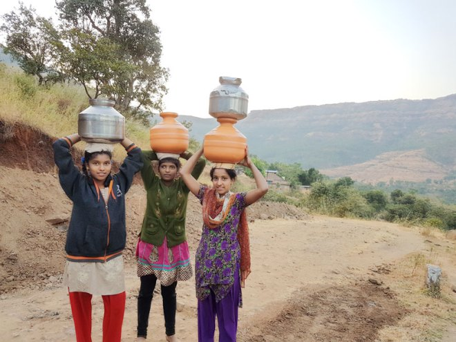 Children carried water to their homes from the foothills prior to Rotary's intervention.