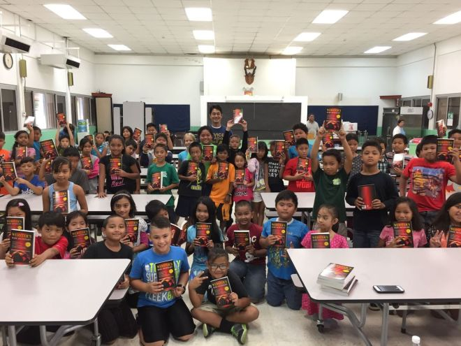 Students at Gregorio T Camacho Elementary School show the dictionaries they received from the Rotary Club of Saipan after the distribution with club vocational services director Wendell M Posadas.