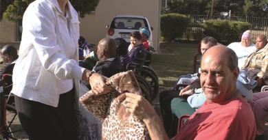 Rotarian Clara du Plessis presents Rudi with a new blanket.