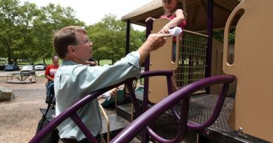 Lancaster Parks and Recreation Superintendent Mike Tharp Jr hands out a T-shirt and pool pass to Aubrey Clark, 5, at Rising Park in Lancaster. Photo: Matthew Berry/Eagle-Gazette)