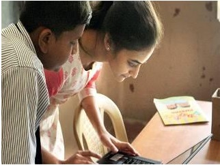 A volunteer works with the student as part of the Mentor India project.
