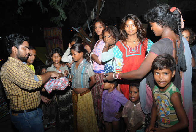 Sanat and Viren, volunteers of the NGO Feeding India, distribute food among children in Bathinda. Photo: Pawan Sharma / Tribune