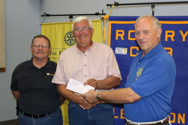 Bernie Svoboda, right, presents a $2,500 cheque from the Lexington Rotary Club to Mike Schulte, left, and Max McFarland, centre, members of the Hero Flight Organising Committee, during a Rotary bi-monthly meeting at the Lexington Public Library. Photo: Kevin Zelaya