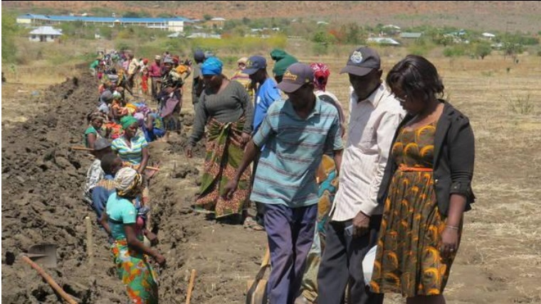 Workers dig trenches to bury water pipes in the village of Masandare in Tanzania as part of the water system project sponsored by Rotary International. Photo: Glenn Rippke