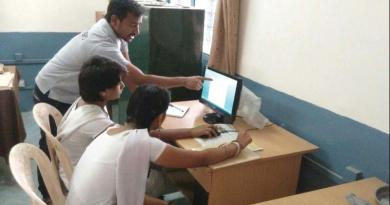 A Shikshan volunteer help government schoolchildren in Bengaluru learn computers and English.