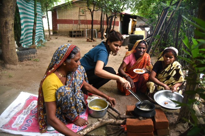Harshita tries her hand in primitive cooking with the locals.