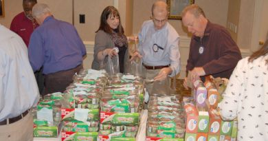 Rotary Club of Gwinnett County members Mary Hester, from left, Sherwin Levinson and Bill McCargo move down a food line to fill bags with food for hungry during the club's Rotary Has Heart project. Photo: By Arrangement