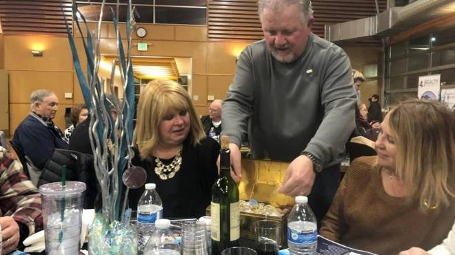 Puyallup-South Hill Rotary past president Jeff Lieurance shows off $9,000 in bullion at the Gold and Silver Reverse Raffle. Photo: Allison Needles