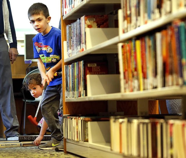 Julien Sitko, 5, watches his golf ball roll between the shelves of books.Photo: Fred Adams/Times Leader