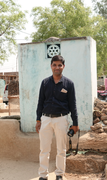 Dinesh Rathore, an RCC member and photographer, in front of a Rotary toilet.