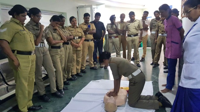 Police personnel getting trained in lifesaving techniques.