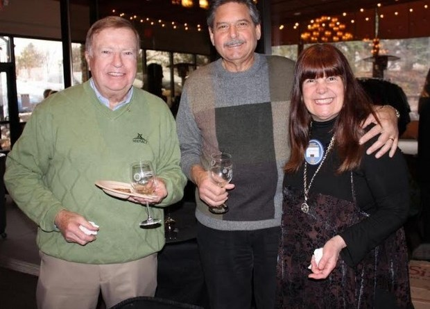 John Hall, left, enjoys food and drink samples from local vendors and breweries with Manny and Lynn Freshman at Taste of the Finger Lakes in Victor. Photo: Dave Luitweiler