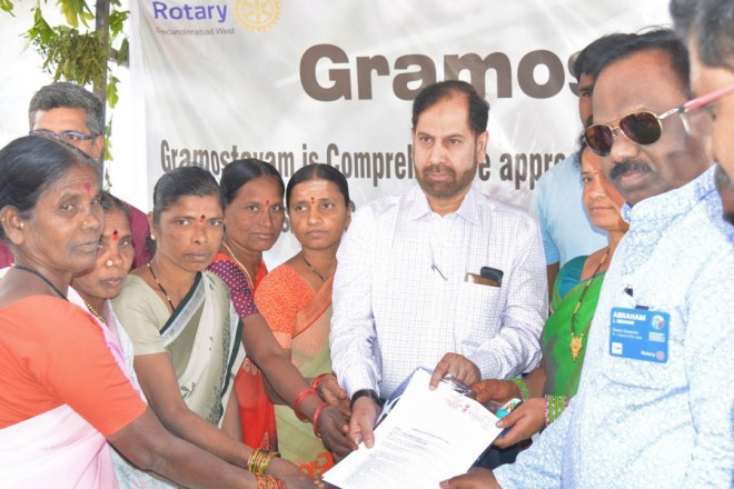 DG J Abraham presents an MoU to the District Collector Syed Omar Jaleel in the presence of the villagers.