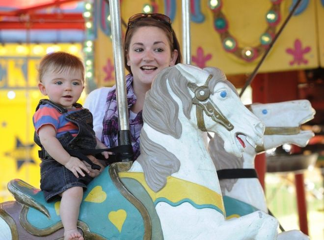 """Jayden Dolin age 7 months rides the Merry-Go-Round with mom, Lucy Clark at West Springfield's """"Taste of the Valley"""" on the town green. Photo: Dave Roback/The Republican"""
